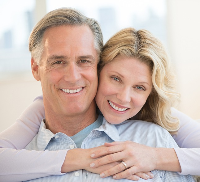 Older woman smiling, embracing man from behind at home