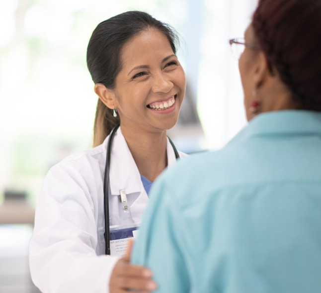 Female Doctor with woman patient, smiling and enjoying conversation