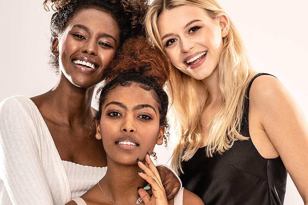 Three attractive young multiethnic women looking at camera, smiling